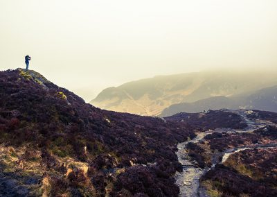 Photographer silhouette on a scottish mountain in a cloudy day